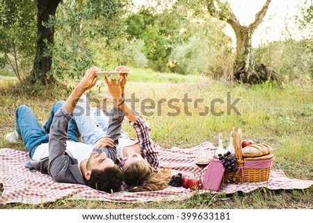 Beautiful Young Couple Using Tablet During Picnic Outdoor