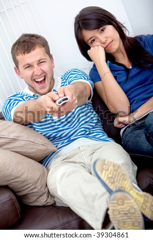 Beautiful young couple watching tv at home - stock photo