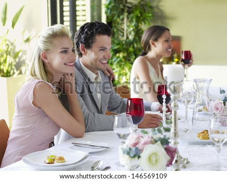 Beautiful young couple with arm around at dinner party - stock photo