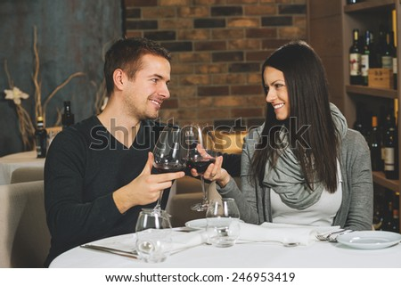 Beautiful young couple with glasses of wine in restaurant - stock photo