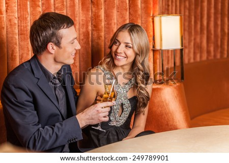 Beautiful young couple with glasses of wine. Young Woman In Restaurant Having Meal - stock photo