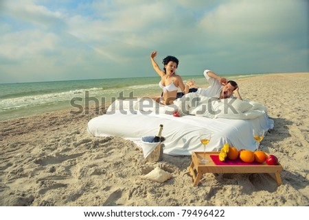 Beautiful young couple yawning in bed in morning on the beach - stock photo