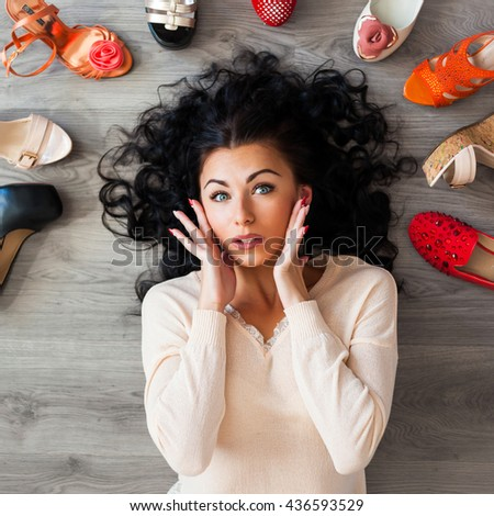 Beautiful young cute funny girl lying on the floor around her laid out different shoes, sandals, ballet flats, a girl can not choose what kind of shoes to wear, shows a surprisingly emotions, top view - stock photo