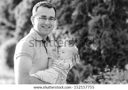 Beautiful young dad taking care of baby boy - stock photo