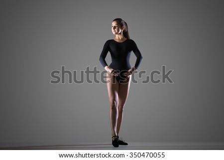 Beautiful young dancer woman in black sportswear working out, dancing, full length, studio, dark background