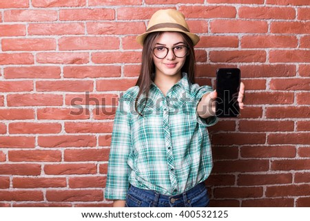 Beautiful young dark-haired girl in casual clothes, hat and eyeglasses posing, smiling and demonstrate on smartphone, standing against brick wall - stock photo