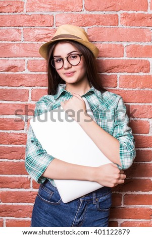 Beautiful young dark-haired girl in casual clothes, hat and eyeglasses posing,  smiling and with close laptop in hands, standing against brick wall - stock photo