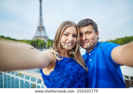 Beautiful young dating couple in Paris making funny selfie near the Eiffel tower