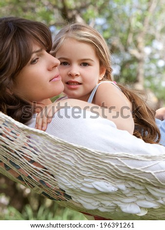 Beautiful young daughter and her mother hugging and enjoying laying together in a hammock during a summer holiday in a home vacation garden during a sunny day. Outdoors healthy  and relaxing lifestyle - stock photo