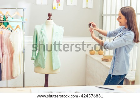 Beautiful young designer is smiling while taking photo of her work using a smartphone, standing in dressmaking studio - stock photo