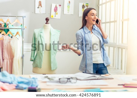 Beautiful young designer is talking on the mobile phone and smiling while standing in dressmaking studio - stock photo
