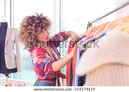 Beautiful young designer near rack with hangers