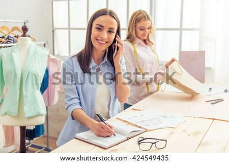 Beautiful young designers are working in dressmaking studio. One girl is making notes, talking on the mobile phone, looking at camera and smiling - stock photo