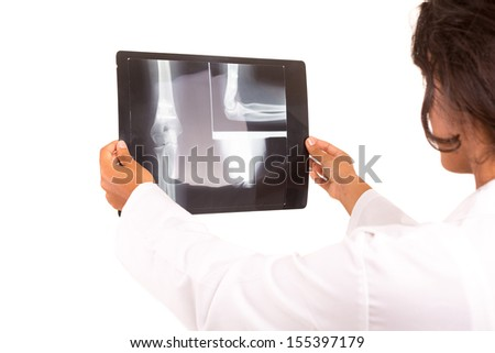 Beautiful young doctor looking at a X-Ray, isolated over white