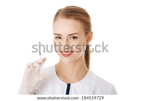 Beautiful young doctor or nurse is holding a needle. Isolated on white. - stock photo
