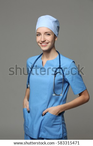 Beautiful young doctor with stethoscope on grey background