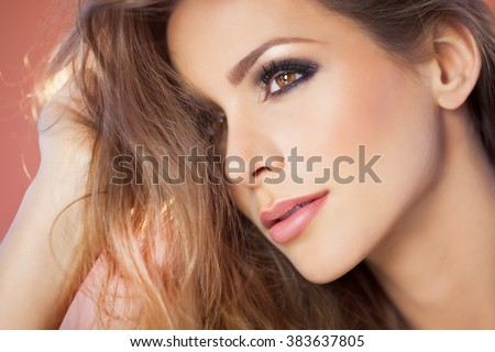 Beautiful young dreamy woman portrait with smoky eyes makeup and long hair.