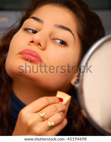 Beautiful young eastern woman putting makeup in front of a mirror