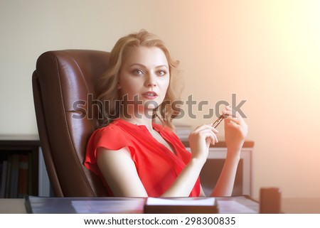 Beautiful young elegant blond business woman sitting in office on brown leather chair in red blouse holding pen in hands looking forward indoor on white background copyspace, horizontal picture - stock photo