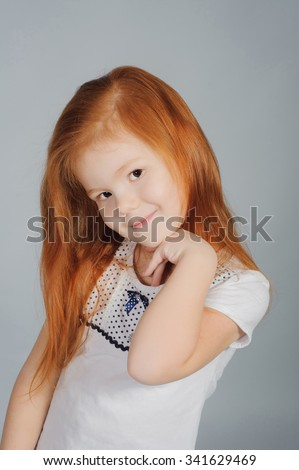 Beautiful young elementary age school girl over grey with long straight red hair in summer clothes. Hands near her face. Smilling little girl in white.  - stock photo