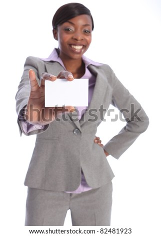Beautiful young ethnic african american business woman with a big happy smile, holding out a business card. Model is blurred in background with card in sharp focus close to camera. - stock photo