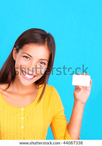 Beautiful young ethnic woman presenting a blank business card, on a bright blue background. - stock photo