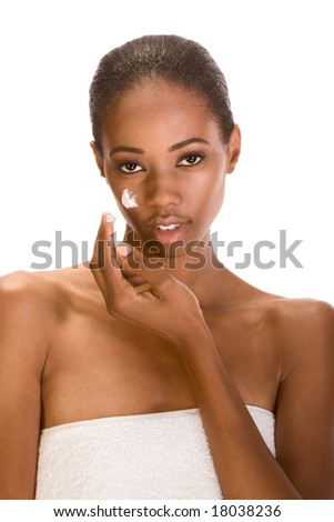Beautiful young ethnic woman with Slicked Back Hair wrapped in white bath towel applying moisturizer on her face - stock photo