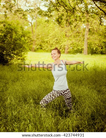 Beautiful young european woman doing yoga in the summer fresh forest.