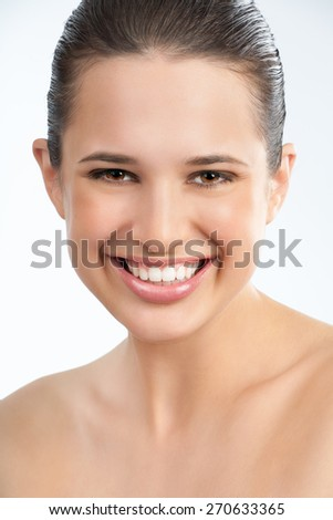 Beautiful young European woman with fresh tanned glowing skin and healthy white teeth. - stock photo