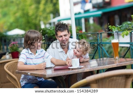 Beautiful young family - a father and two children, adorable baby girl and a school boy, laughing and talking enjoying a drink in an outside cafe in summer in an old city center in Germany - stock photo