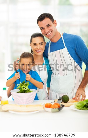 beautiful young family cooking in kitchen at home - stock photo