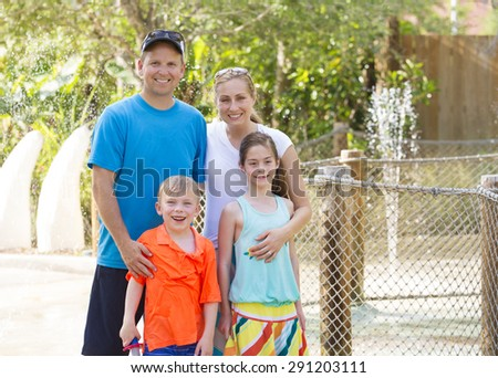 Beautiful young family enjoying a day at an outdoors amusement park - stock photo