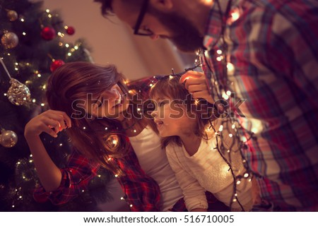 Beautiful young family enjoying their holiday time together, decorating Christmas tree, arranging the christmas lights and having fun