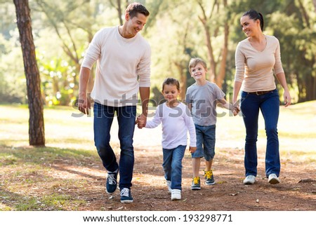 beautiful young family hand in hand walking in park - stock photo