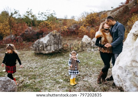 beautiful young family in the mountains in autumn. walk near the stones and yellow trees. family happiness. two daughters and parents