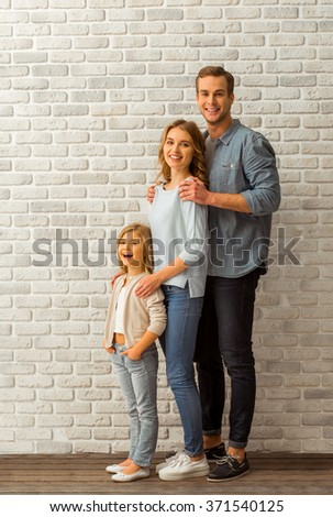 Beautiful young family looking in camera and smiling while standing in line against white brick wall - stock photo