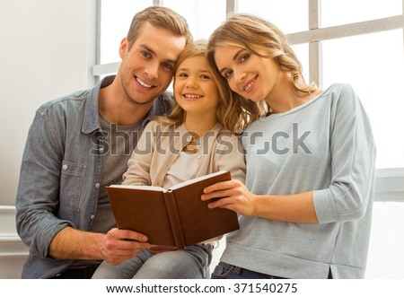 Beautiful young family looking in camera, smiling and holding a book while sitting near the window at home - stock photo