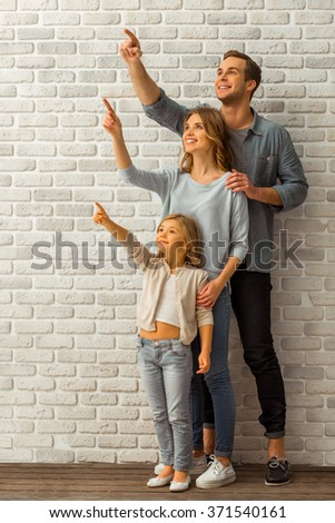 Beautiful young family looking up, smiling and pointing while standing in line against white brick wall - stock photo