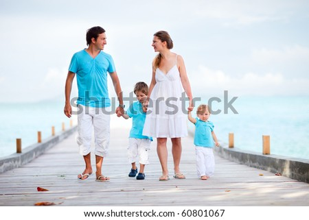 Beautiful young family of four walking along wooden jetty