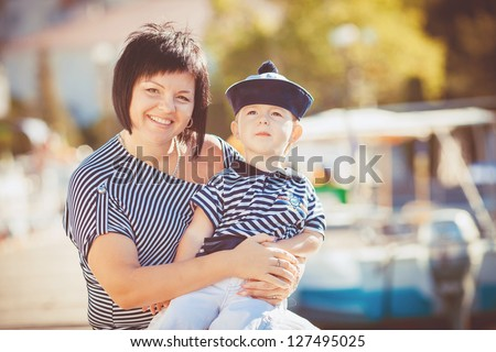 Beautiful young family of two walking along wooden jetty/ Woman with son on pier - stock photo