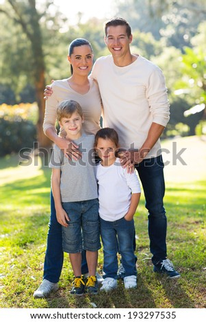 beautiful young family portrait outdoors in park - stock photo