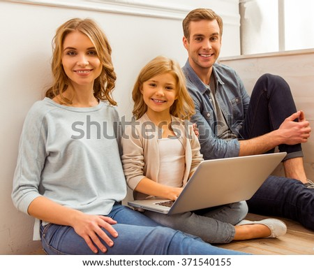 Beautiful young family using laptop and smiling while sitting on floor near the window at home