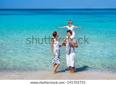 Beautiful young family walking on a tropical beach - stock photo