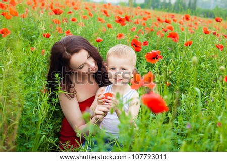 Beautiful young family walking on the poppy field in summer.