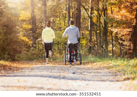 Beautiful young family with baby in jogging stroller running outside in autumn nature