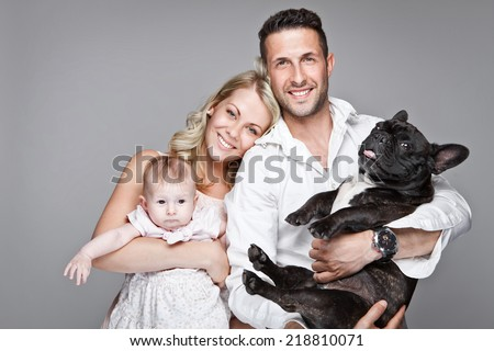 beautiful young family with little baby and dog isolated over grey background - stock photo