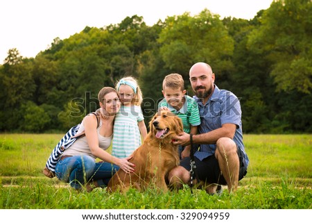 Beautiful young family with their pet dog, golden retriever - stock photo