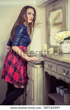 Beautiful young fashion caucasian model in blue and red and scottish cell dress and fashion makeup and hairstyle posing next to commode smiling and looking at camera in provence design interior.