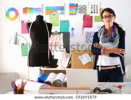 Beautiful young fashion designer standing in studio