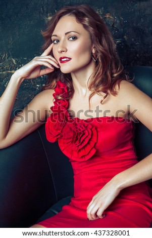 Beautiful young fashion model in red dress and fashion makeup and hairstyle posing sitting in the armchair near the artificial fireplace and looking at camera. Studio shot.